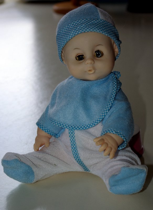 An old baby doll in a blue and whtie outfit.