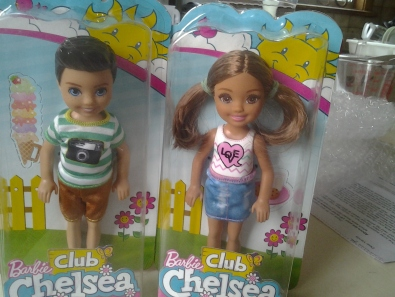 Two small dolls inside their packaging