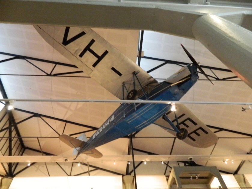 Looking up at a plane suspended from the roof at QVMAG Launceston