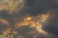 Sun through smoke tinged clouds.